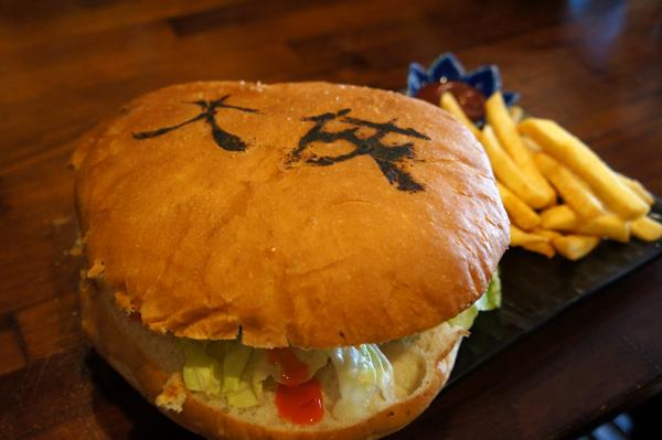 漢堡看起來很豪邁,上頭還有字樣,第一時間就想拿起來比...