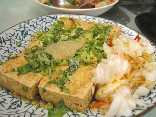 招牌臭豆腐,一份有六塊,上頭擺滿蔥花、蒜泥,旁邊有泡菜
