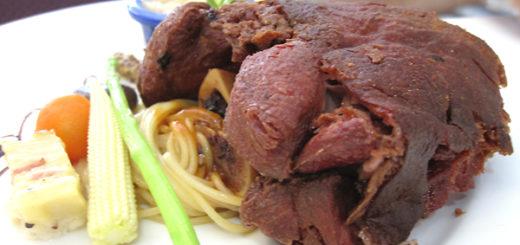 德國豬腳全貌,旁邊有配菜,底下有一些麵條