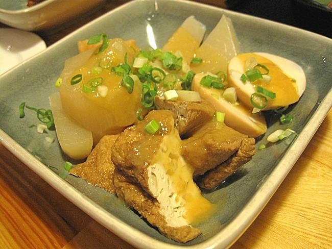 日式關東煮,有油豆腐、蛋、蘿蔔等。上頭淋上的醬汁帶著薑汁味道....